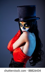 Sugar skull girl in tophat and red dress, studio shot