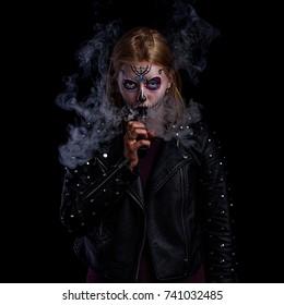 Sugar skull girl.Sexy woman is vaping. Studio shooting.