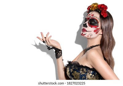 Sugar skull makeup. Halloween party, traditional Mexican carnival, Santa Muerte. Beautiful young woman costume, painted face. Model girl pointing hand, isolated on white background. Calavera  Catrina