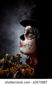 Sugar skull woman in tophat, holding dead roses, studio shot