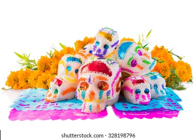 "sugar skulls used for ""dia de los muertos"" celebration isolated on white with cempasuchil flowers"
