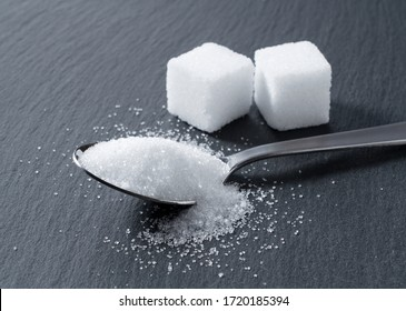 Sugar in a spoon placed on a black background