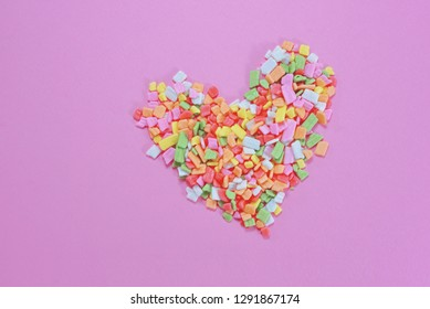 Sugar sprinkle in heart shapes on pink pastel background. Flay lay of sweet sugar bakery decoration with copy space for designed work.Love and romantic concept for Valentine Day. Minimal Style.