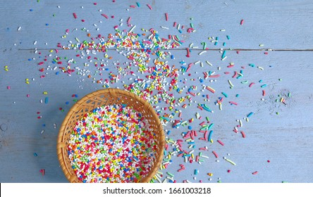 Sugar Sprinkles. Isolated. Colourful sugar sprinkles for cakes and bakery on a blue wooden surface. Stock Image.