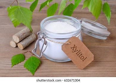 sugar substitute xylitol, a glass jar with birch sugar, liefs and wood on wooden background