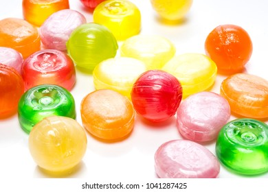 Sugar sweets. Beautiful colorful and delicious lollipops, marmalade and jelly different shapes and composition isolated on abstract blurred white background. Closeup with soft selective focus
