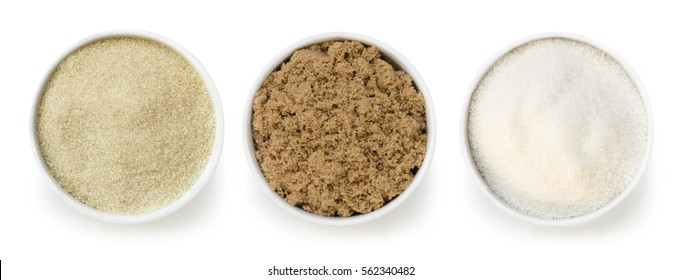 Sugar varieties in small bowls, isolated, top view.  Includes raw, brown, and white.