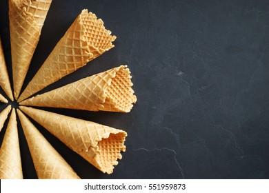 sugar waffle cone ice cream arranged in pattern on dark background