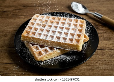 Sugar waffles presented on a black plate and over a wooden board
