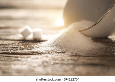 sugar in white cup on wood table.Vintage tone retro filter effect,soft focus(selective focus)
