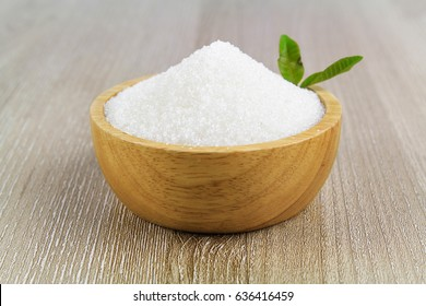 Sugar in wooden bowl isolated on white