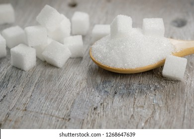 Sugar in wooden spoon for putting in coffee, adding sweetness - image