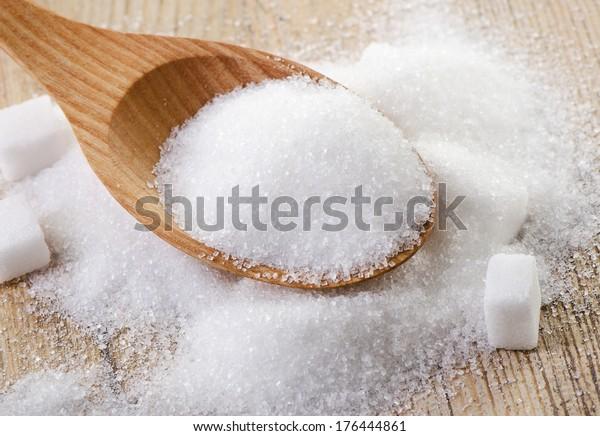 Sugar in a wooden spoon . Selective focus