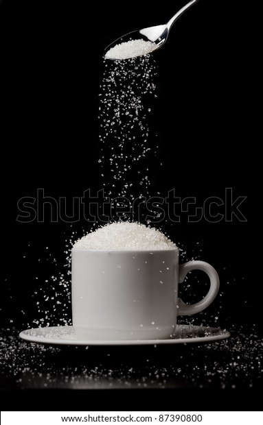 Sugarfall. A cup of coffee with a hill of sugar and a spoon. Concept of addiction to sugar.  Black and white photo.