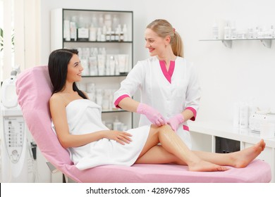 Sugaring: Beauty Concept. Hair removal on legs. Young beautiful woman with dark hair gets the procedure for hair removal liquid sugar. Beautician Giving Epilation To Woman On Thigh