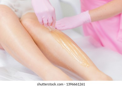 sugaring concept. beauty saloon. woman legs hair removing. hands in pink rubber gloves
