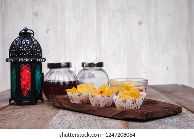 Suger, lantern, butter,  cornflakes cup, honey on  wooden background
