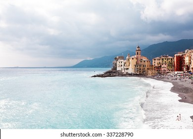 Suggestive view of San Rocco, Italy. Blue sea with big waves breaking on the beach and people taking bath. Travel, vacation concept