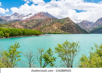 Sughd Iskanderkul Lake Breathtaking Picturesque View with Shore Houses and Snow Capped Mountains on a Sunny Blue Sky Day