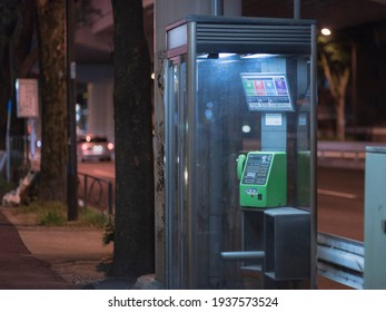 Suginami City, Tokyo, JAPAN - August 11th, 2020: Urban night scene of a telephone booth along the road with anyone.