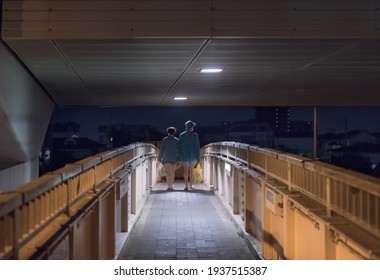 """Suginami, Tokyo,  JAPAN - June 8th, 2020: Night view of a couple of young Japanese walking on a sidewalk platform above the road called """"koshukaido"""" and the Tokyo Expressway over them."""