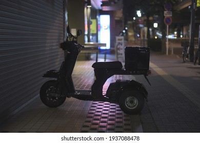 Suginami, Tokyo,  JAPAN - May 13, 2020: A Scooter moped bike parked in front of a closed shop in the streets of Tokyo with blur in the background, by night, a beautifull pink color luminous reflection