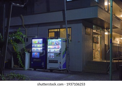 Suginami, Tokyo, Japan - May 30th 2020: Two drinks vending machines along a Showa style Japanese mansion by night.