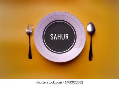 suhoor or sahur (in bahasa) text in white plate with spoon and fork,top view in yellow background. Sahur is the meal consumed early in the morning by Muslims before fasting