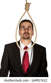 Suicidal businessman contemplating hanging standing looking at a hangmans noose