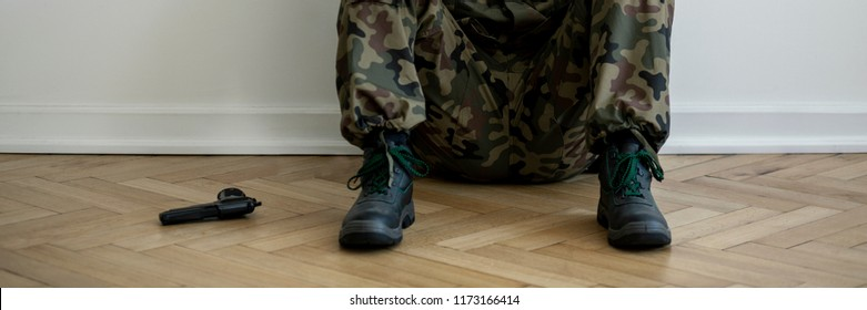 Suicidal thought after returning from war concept. Anonymous soldier in uniform sitting on the floor with a gun next to him
