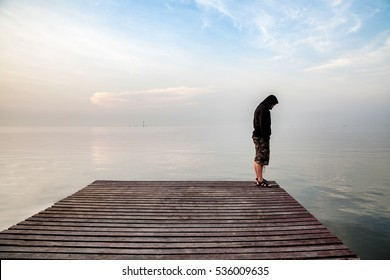 Suicide concept, Depressed young man wearing a black hoodie standing on wooden bridge extended into the sea looking down at his shoe and contemplating suicide., On the edge of a bridge with sea below.