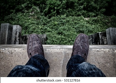 Suicide and Major depressive disorder concept., Depressed young man looking down at his shoe and contemplating suicide., On the edge of a high bridge with forest below.