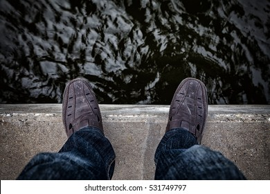 Suicide and Major depressive disorder concept., Depressed young man looking down at his shoe and contemplating suicide., On the edge of a bridge with river below.