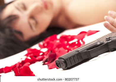 Suicide naked woman lying on the floor with gun and metaphoric blood