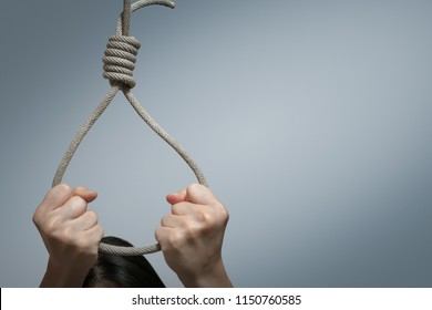 Suicide prevention concept, Depressed young asian woman wearing a noose around her neck for kill her self isolated on gray background, copy space with clipping path.