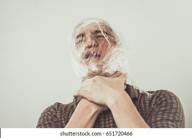 Suicide Young Man in Plastic Wrap Strangling Yourself With Your Hands