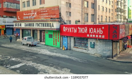 Suifenhe town, Heilongjiang province, China-January 31, 2018: Winter windy morning in the trade quarter frontier town. The information signs of Hotel Haoshen and Fruit shop are in Russian and Chinese