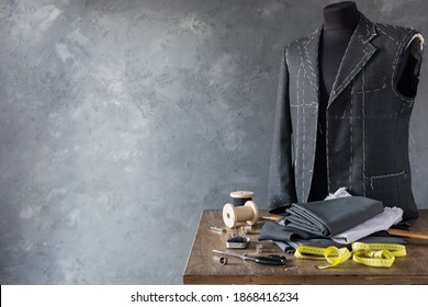 suit jacket on male tailor mannequin and sewing tools, creative concept of clothes atelier