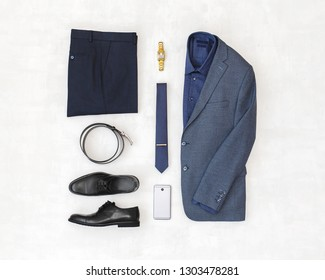 Suit jacket, pants, blue shirt, black shoes, belt, watch, necktie, smartphone. Overhead view of classic elegant formal men's outfit. Set of stylish men's clothes and accessories. Flat lay, top view.