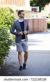 Suit jacket and shorts guy in shades, walking
