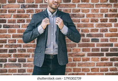 Suit man smart casual outfit young businessman adjusting collar of his blue wool blazer with shirt against brick wall background at office. Urban lifestyle.