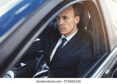 Suit wearing man looking forward while driving car. Horizontal outdoors shot.