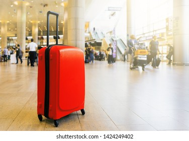 Suitcase in airport airport terminal waiting area with lounge zone as a background. Traveling luggage in airport terminal. Vacation theme concept. Image is with copy space