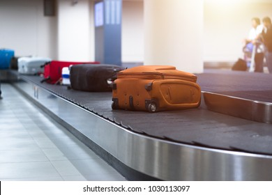 Suitcase or baggage on luggage conveyor belt in an arrivals lounge of airport terminal. Selective focus.