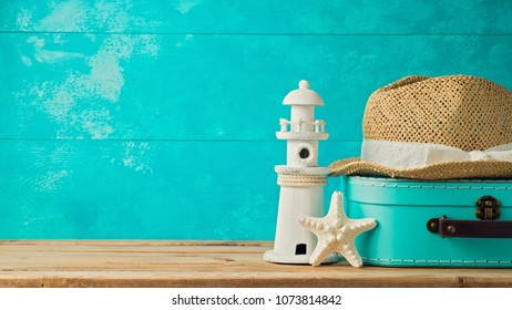Suitcase box, hat and lighthouse decor over wooden background. Summer vacation concept