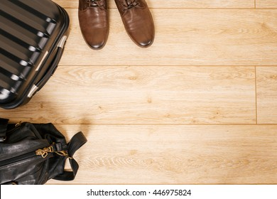 suitcase with clothes, bag and shoes lying on the floor at home.