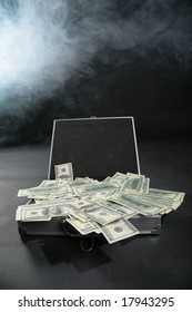 Suitcase with dollars against smoke