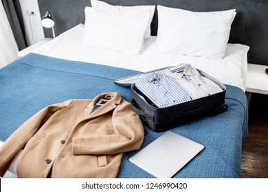 Suitcase full of clothes with coat on the bed of the hotel room or bedroom. Business trip concept