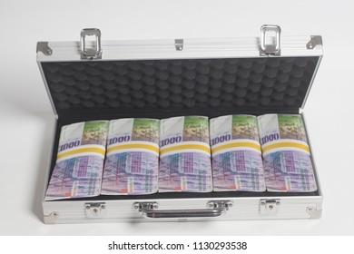 Suitcase full of one thousand Swiss franc on white background