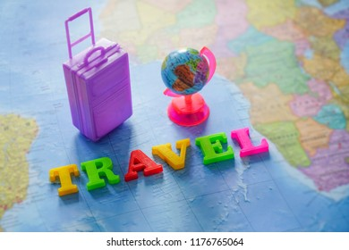 suitcase, globe map and world - travel made from colorful letters lie on world map background.
